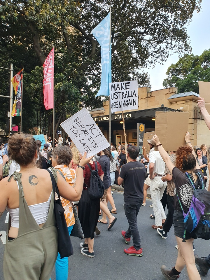 Protesters march in Sydney. One sign reads: Make Australia green again. Another sign reads: act before it's too late