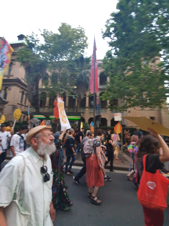 Protesters march in the Sydney CBD. In teh forefront is an older man with a white beard