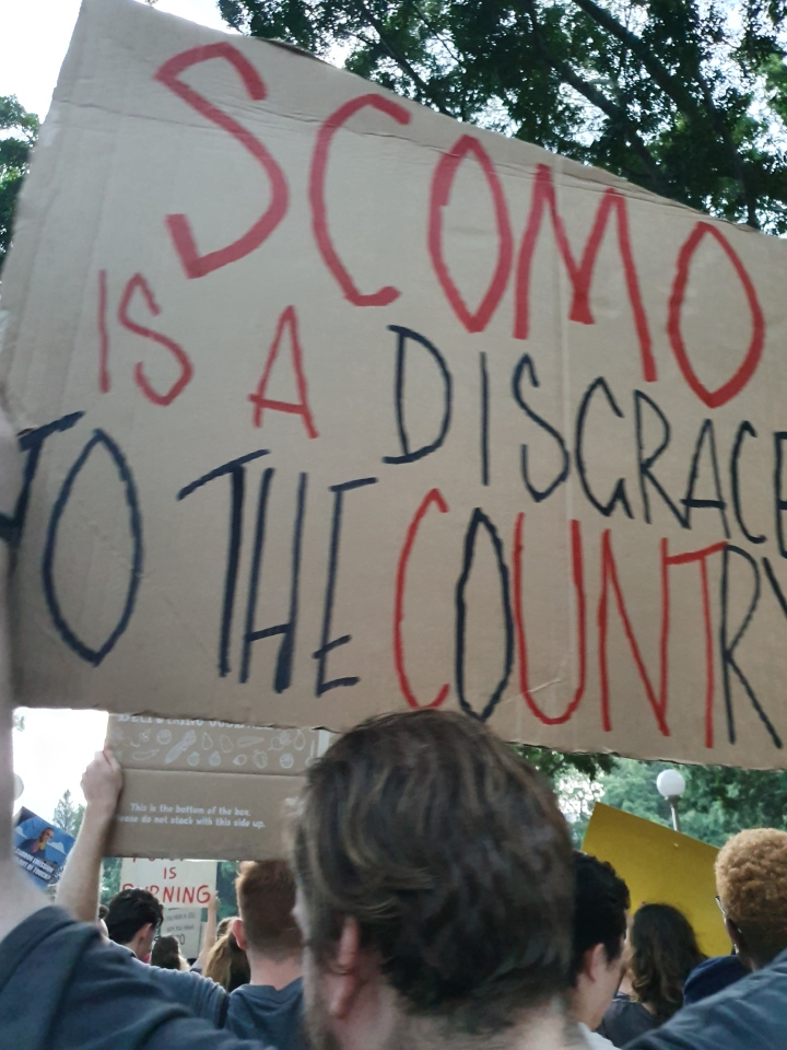 Protester holds up a sign that reads: Scomo is a disgrace to the country