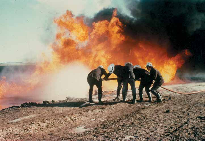 Five firefighters are bent over a fire hose, with a large blaze behind them and a large wall of black smoke