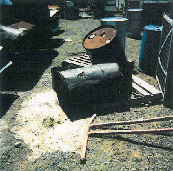 Corroded drums are thrown on their side and upside down in the front, while several other barrels are in the background