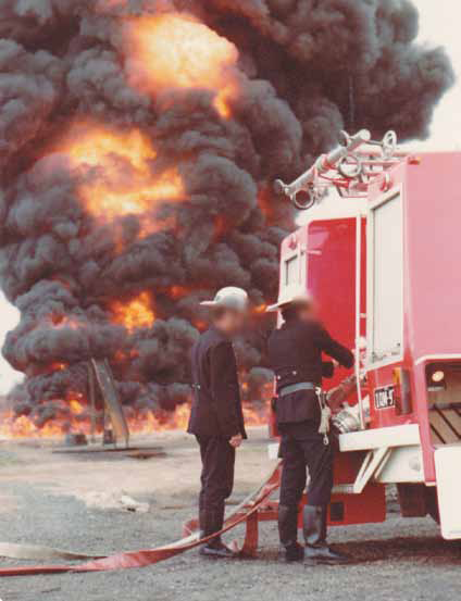 Two firefighters adjust the fire hose at the back of a fire truck while a large black blaze is in the background