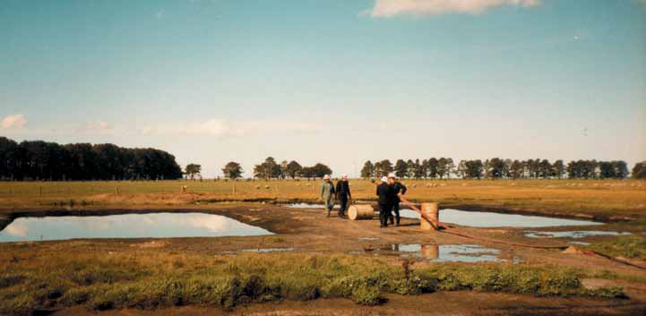 Men in overalls in the background are holding a firehose in a large open field, with large pools of water in the ground