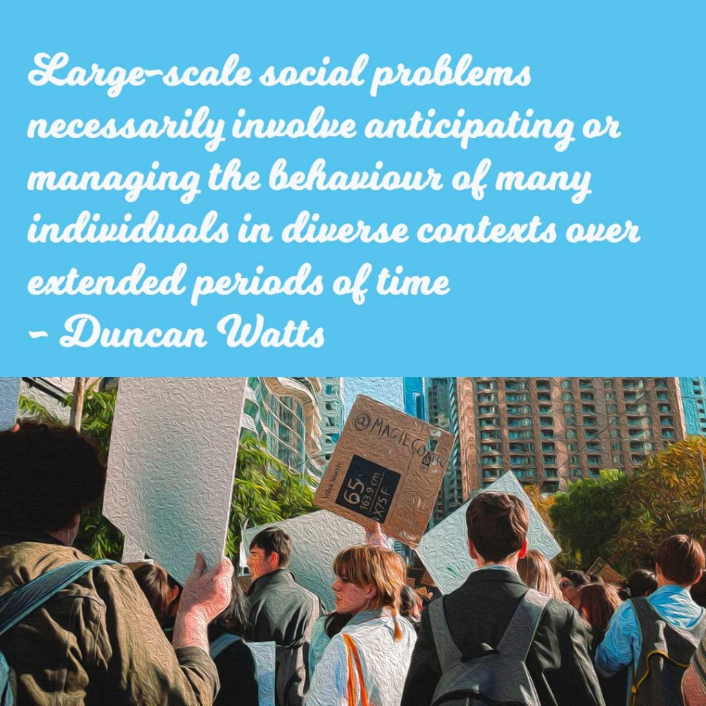 """Protesters hold up signs. Quote from Duncan Watts reads: """"Large-scale social problems necessarily involve anticipating or managing the behaviour of many individuals in diverse contexts over extended periods of time."""""""