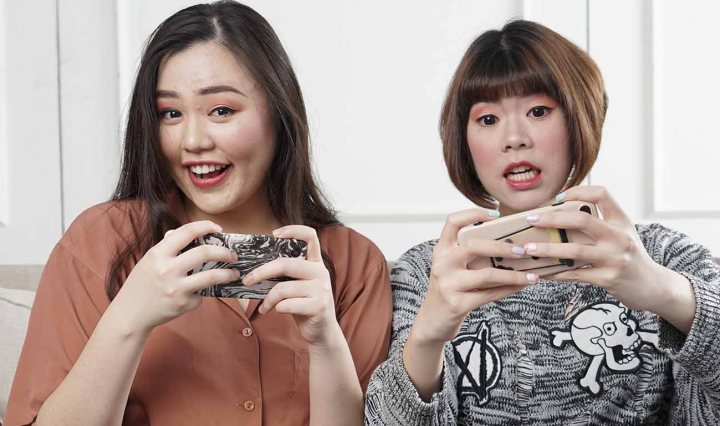 Two Asian women are playing a game on their mobile phones and they looked amused