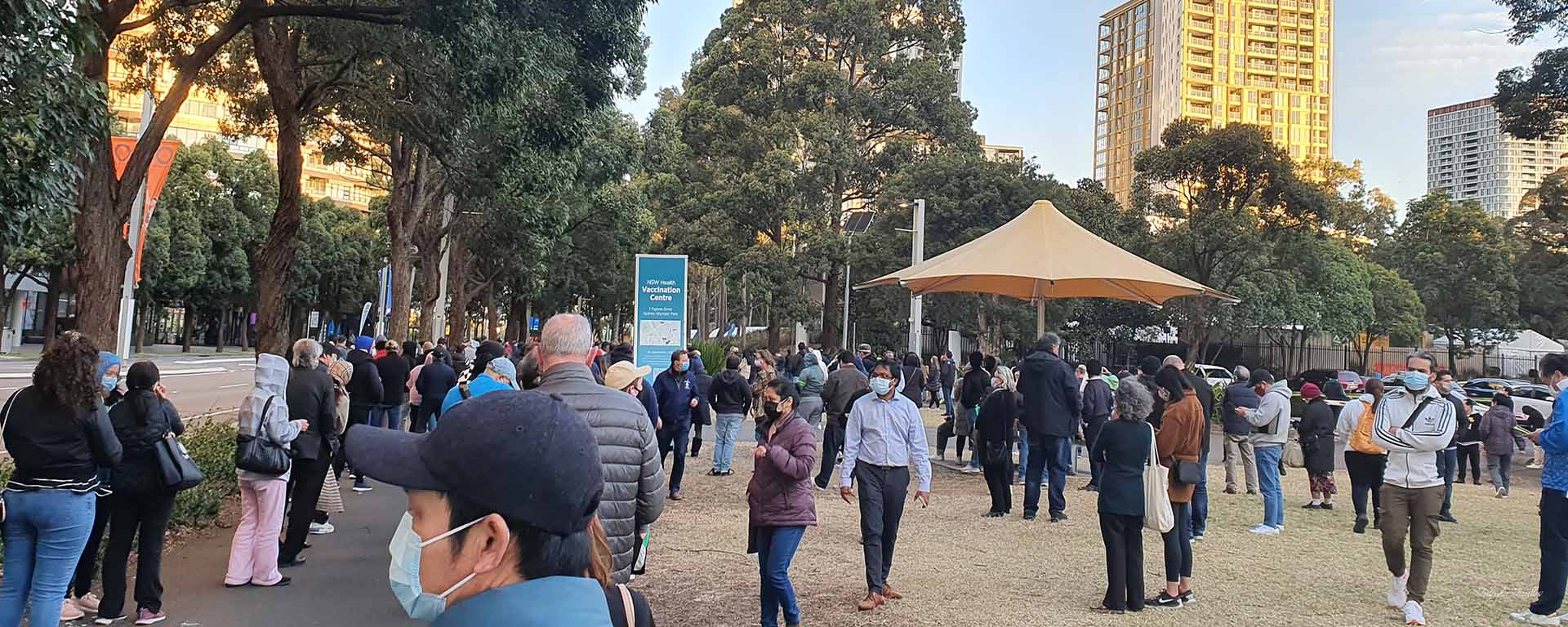 People in face masks line up in a large park