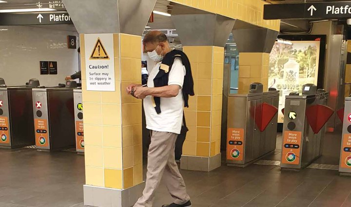 """A Brown man walks across Central Station wearing a face mask. A sign behind says """"Caution"""""""