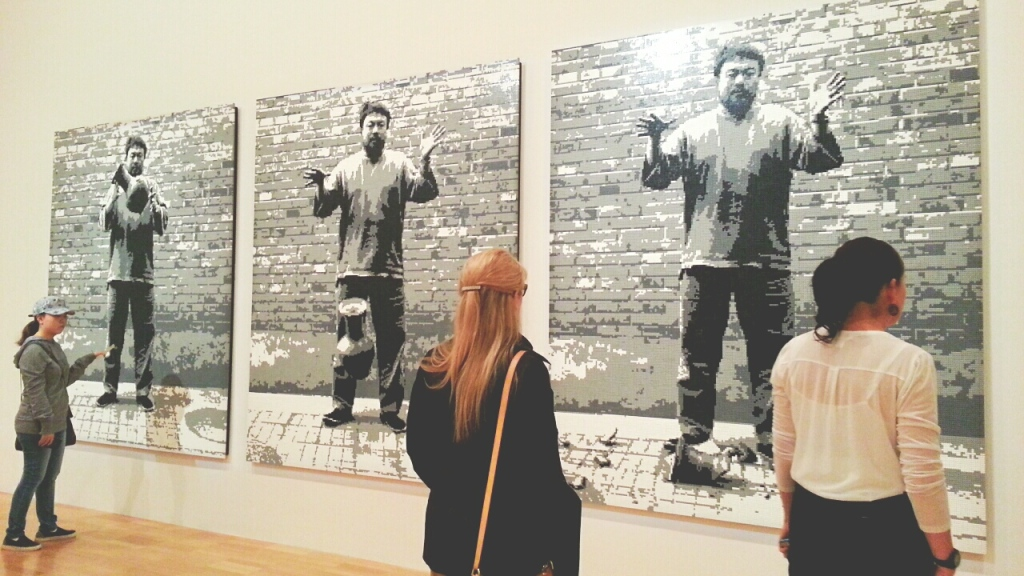 Large digital images hung on a gallery wall showwork three images of the artist, Ai Weiwei dropping a vase. Women stand and look at the art