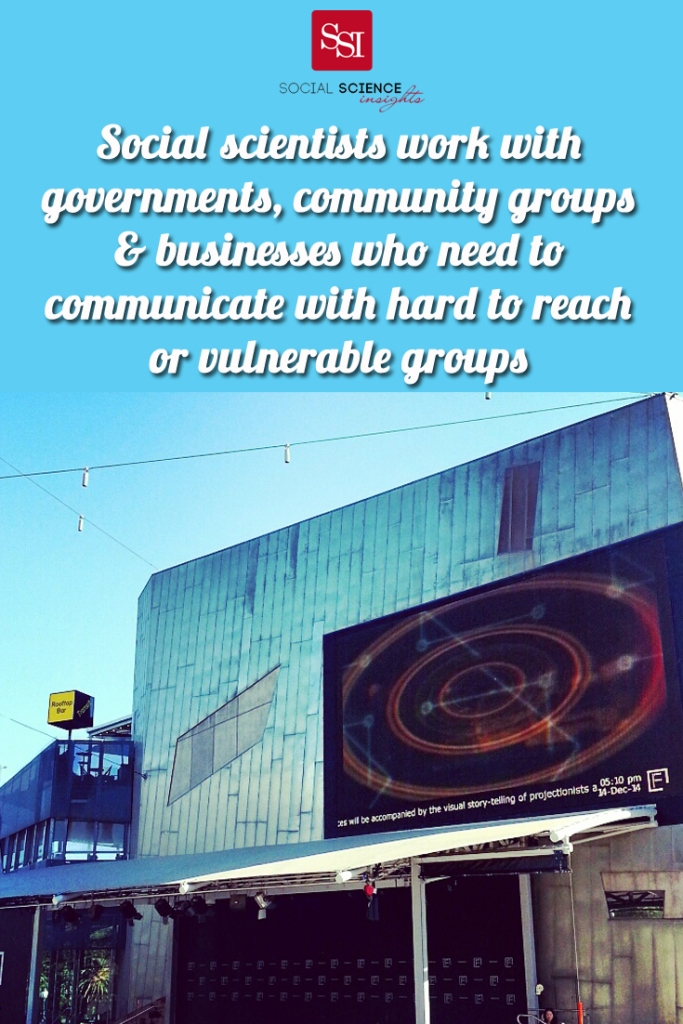 A circle projected on the roof of Watergardens. Quote at the top reads: social scientists work with governments, community groups, and businesses who need to communicate with hard to reach or vulnerable groups